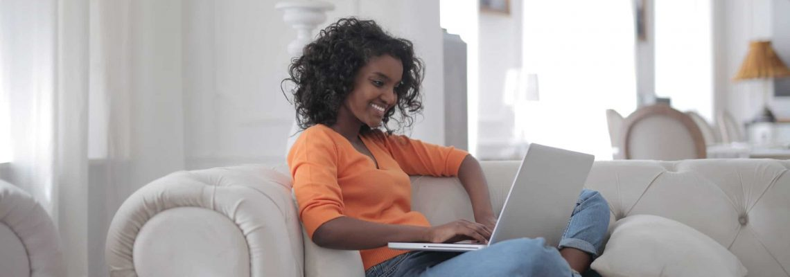 woman-sitting-on-white-couch-using-laptop-computer-3960127